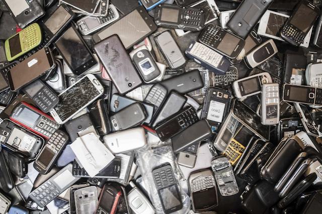 A imagem mostra vários celulares antigos e novos, descartados em um lixão.