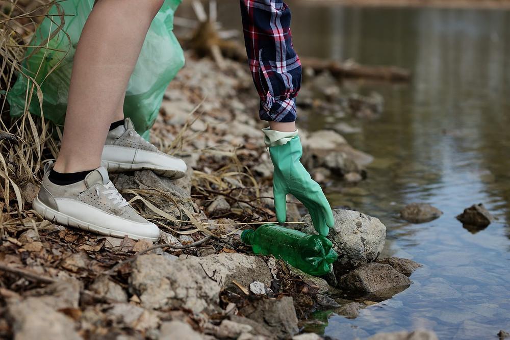 Uma pessoa pega uma garrafa pet da beira de um rio.