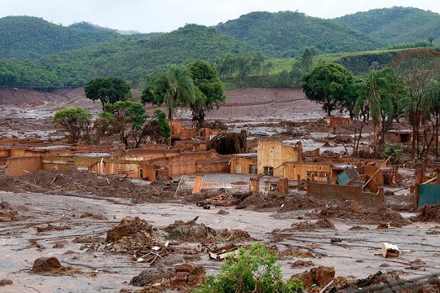 A foto mostra a cidade de Mariana cheio de lama pesada. A lama cobre as casas, vegetação e passa por cima de tudo.