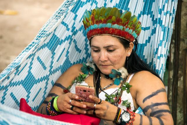 A foto mostra uma mulher indígena deitada em uma rede mexendo em um smartphone. Ela está pintada nos braços, veste um biquíni de crochê e usa pulseiras.