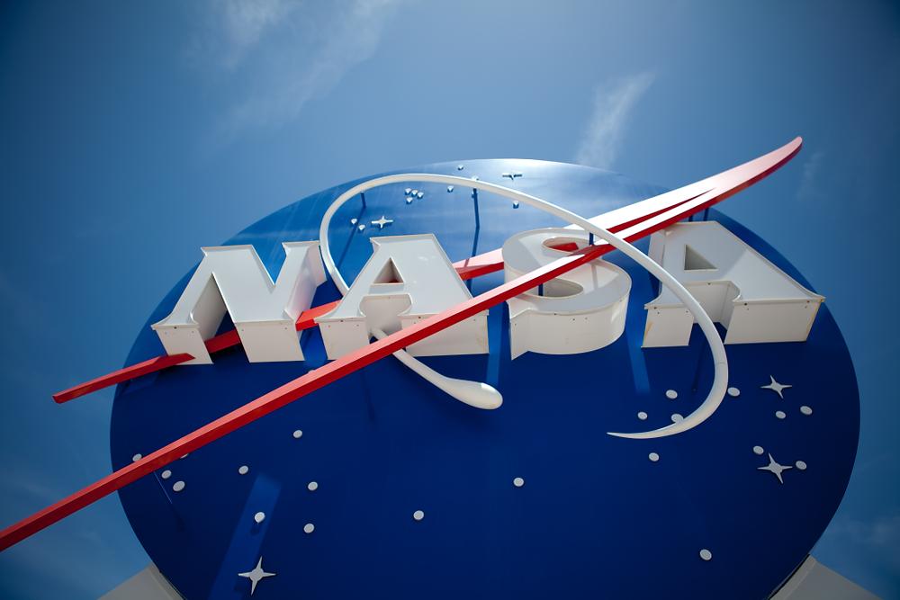 A imagem mostra uma foto do símbolo da NASA. É um círculo azul, com estrelas brancas, escrito NASA em branco com um risco vermelho passando pela palavra.