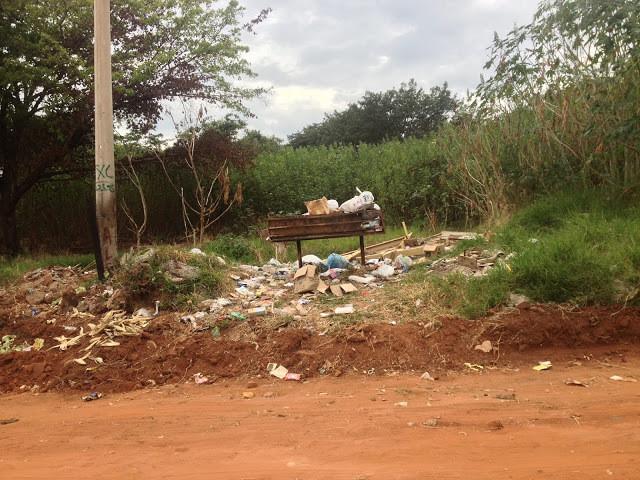 A foto mostra um terreno baldio cheio de lixo jogado. Tem uma lixeira mas ela já está lotada e o entulho cai pelo chão. A vegetação cerca o terreno.