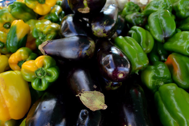 A foto mostra pimentões verdes à direita, berinjelas pretas no meio e pimentões amarelos à esquerda. Estão todos juntos.