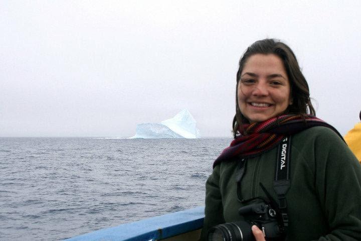 A foto mostra uma mulher, branca, cabelos castanhos lisos, sorrindo, ela veste um casaco e cachecol e segura uma câmera no pescoço. Ela está em um barco e o oceano está ao seu lado.