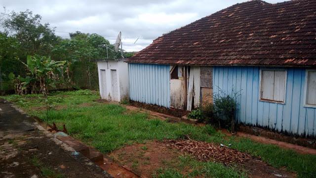 A foto mostra uma casa com paredes azuis e ao lado um chão com grama.