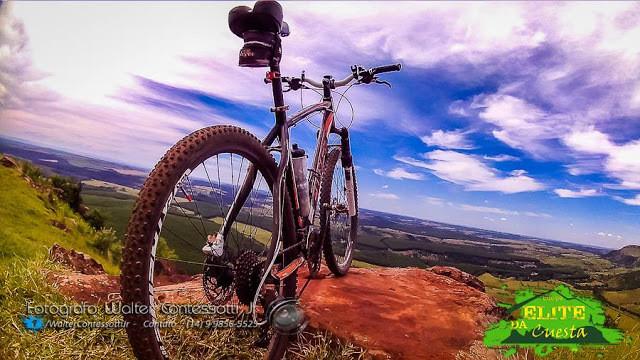 A foto mostra uma bicicleta em cima de um morro grande.