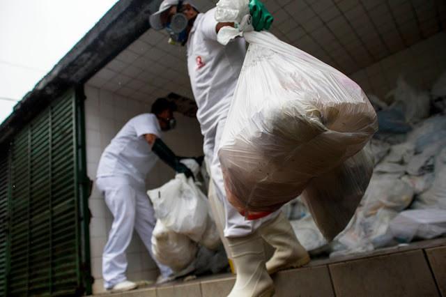 Homens carregam sacos de lixo hospitalar