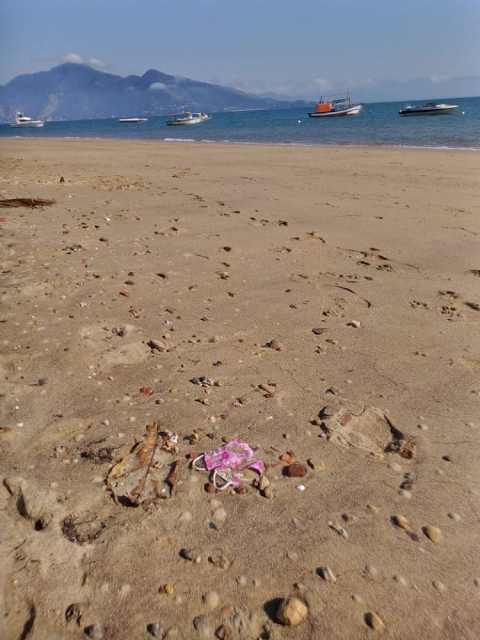 A imagem mostra uma praia. Ao fundo, o mar azul com um morro atrás. Em primeiro plano se vê a areia com máscaras descartadas incorretamente.
