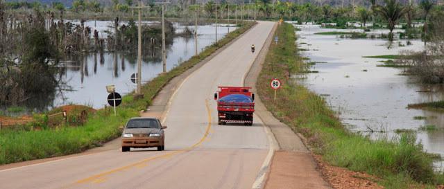 A foto mostra uma estrada com dois carros passando.