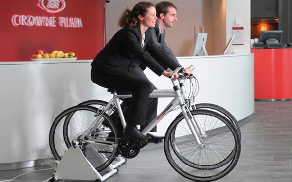 A foto mostra um homem e uma mulher pedalando cada um em uma bicicleta. Os dois são brancos e usam terno.