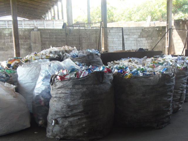 A foto mostra grandes sacos cinzas e brancos cheios de lixo reciclável, como garrafas pets e latas. Os sacos estão em um galpão, no fundo se vê as paredes não pintadas, o dia está ensolarado.