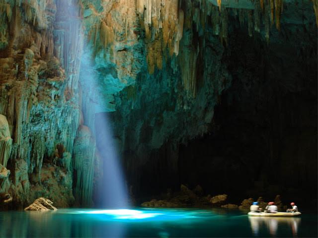Pessoas dentro de um bote em uma caverna aquática. Uma luz entra por cima