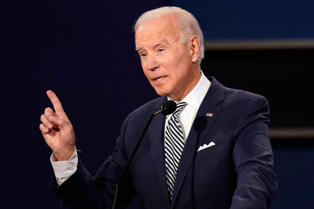A foto mostra Biden: homem, branco, idoso, cabelos brancos, olhos claros e veste terno. Ele está com o dedo indicador levantado.
