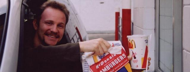 A foto mostra um homem branco, de barba e bigode, ele usa uma blusa comprida marrom. Ele está dentro do carro sorrindo e pegando comida fast-food de um drive-thru.