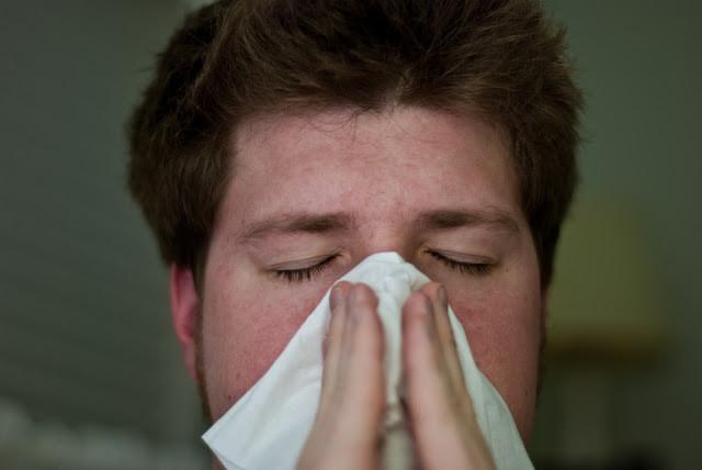 A foto mostra um homem branco, cabelo castanho, assoando o nariz com um pano branco.