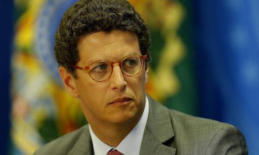 A imagem mostra o ministro do meio ambiente Ricardo Salles com uma cara que aparenta preocupação. O fundo está com o símbolo da República desfocado.