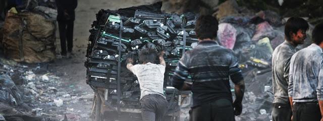 Uma menina empurra um carrinho cheio de equipamentos eletrônicos.