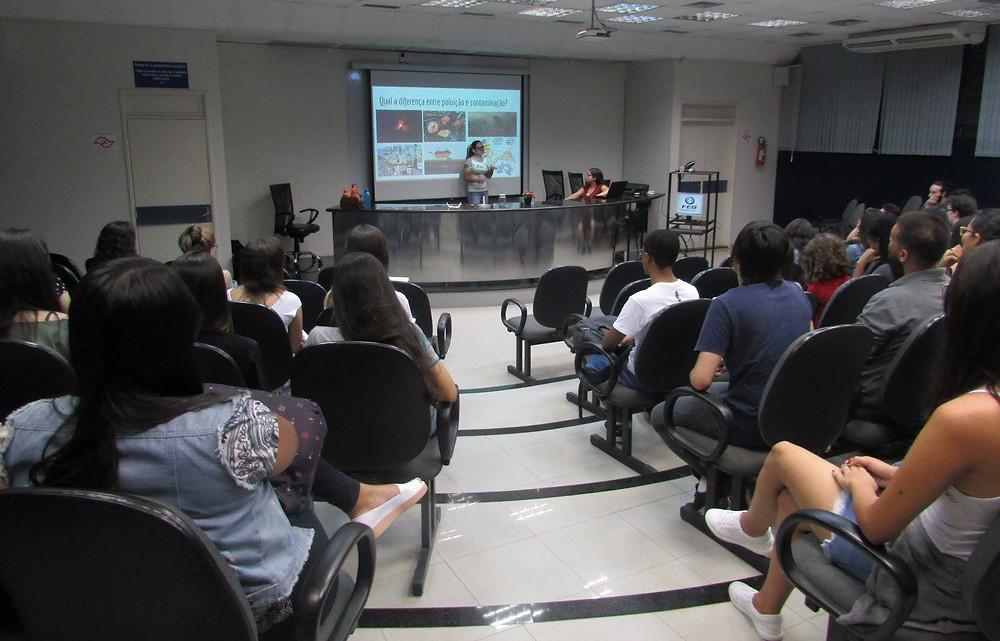 Estudantes de cursinho pré-vestibular assistem à aula, estão sentados e a professora em pé explicando.