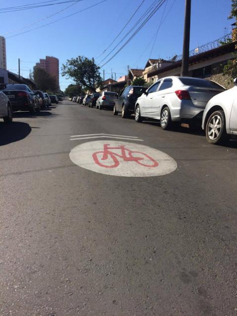 Na rua está pintada uma bicicleta indicando que aquilo ali é uma ciclofaixa