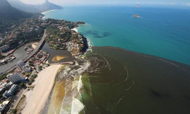 A foto mostra o litoral carioca com o mar azul mas tem uma grande mancha marrom de esgoto no mar.