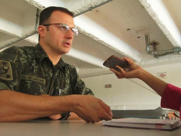 Homem branco, meia idade, cabelo cortado, usa óculos quadrados e usa farda militar.