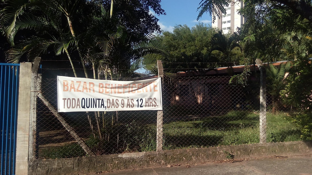 Uma faixa avisando: Bazar beneficente toda quinta, das 9 às 12 horas.