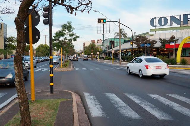 A foto mostra um carro branco passando pela avenida perto do mercado Confiança.