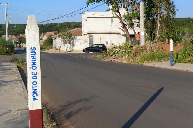 """A foto mostra uma estaca no chão escrito """"ponto de ônibus"""", tem uma estaca em cada lado da rua. Ao fundo se vê uma casa toda branca e um carro preto."""