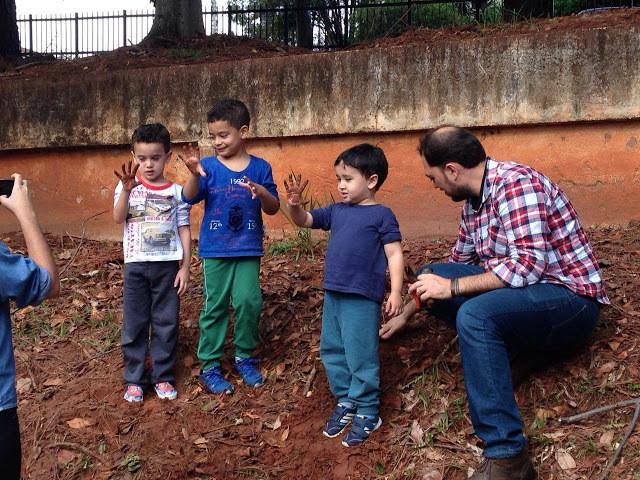A foto mostra três crianças mostrando as mãos sujas de terra porque plantaram árvores.