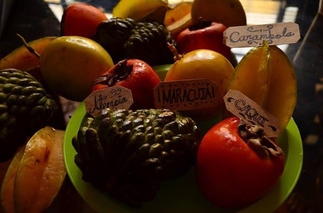 A foto mostra algumas frutas dentro de uma tigela: fruta do conde, caqui, carambola e maracujá.