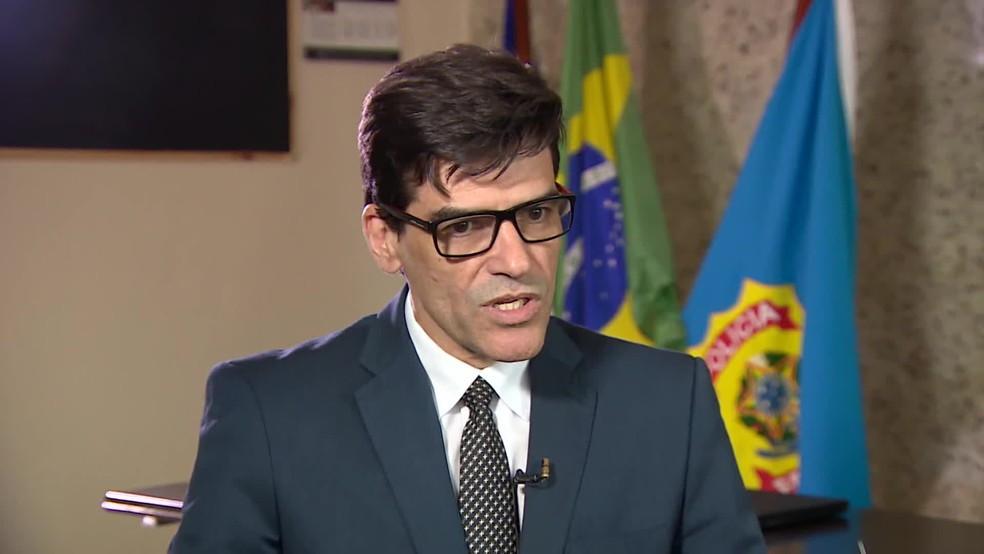 O delegado Alexandre Saraiva aparece do tronco para cima, tranjando paletó e gravata enquanto é entrevistado