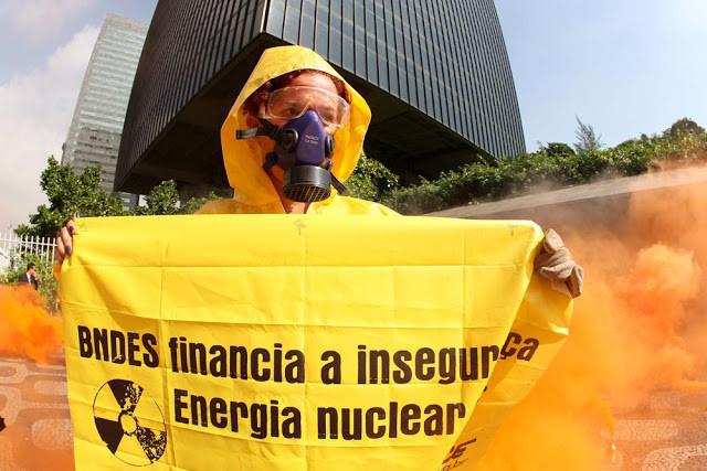 A foto mostra uma pessoa usando máscara de gás e segurando um cartaz: BNDES financia a insegurança