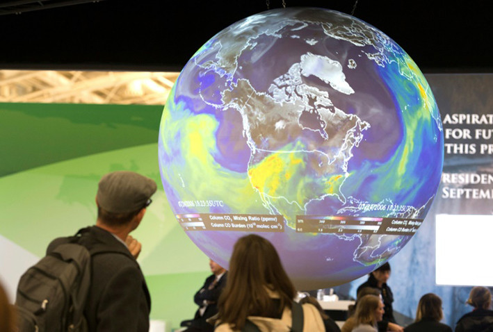 Jovens olham para uma maquete do planeta Terra.