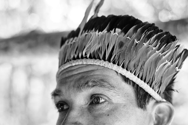 Foto em preto em branco de um índio Kaiowá. O índio está com um cocar e olhando ao longe. A foto foca somente do nariz pra cima.
