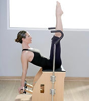 Pilates student performs a Pilates exercise on a Wunda chair