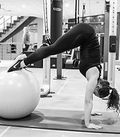 Pilates instructor performing an abs exercise using a Swiss Ball