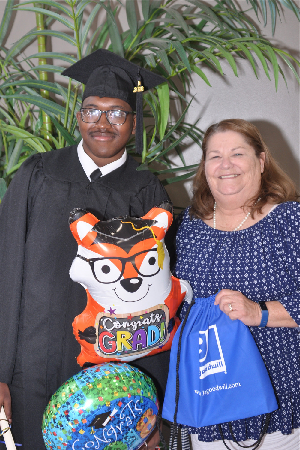 Instructor Susan Dollison poses with HiSET graduate Kendrick Francis and his graduation balloons