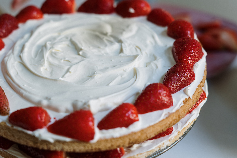Image Description: A cake with white frosting and strawberries