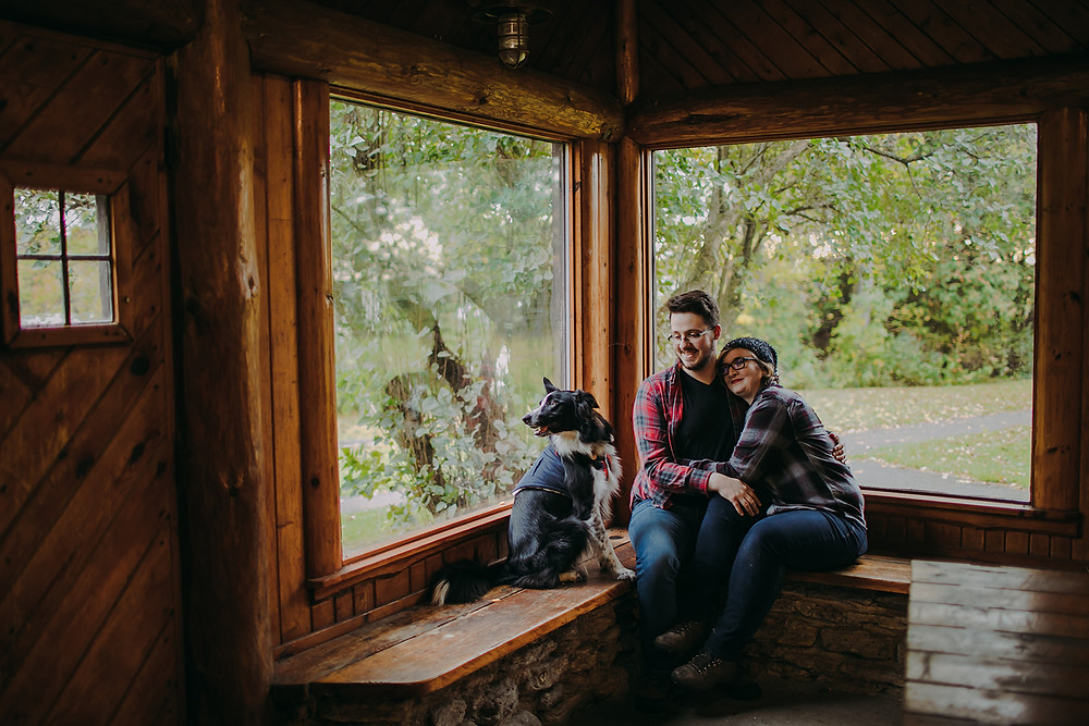 A man, woman, and dog cuddle up inside a log shelter on Peninsula State Park campgrounds