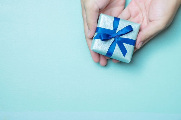 Hands holding blue wrapped gift box with blue ribbon as a present for Christmas, new year,