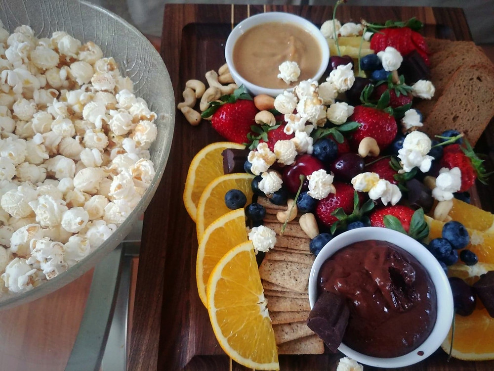 Vegan charcuterie board with fresh fruit, nuts, crackers and popcorn
