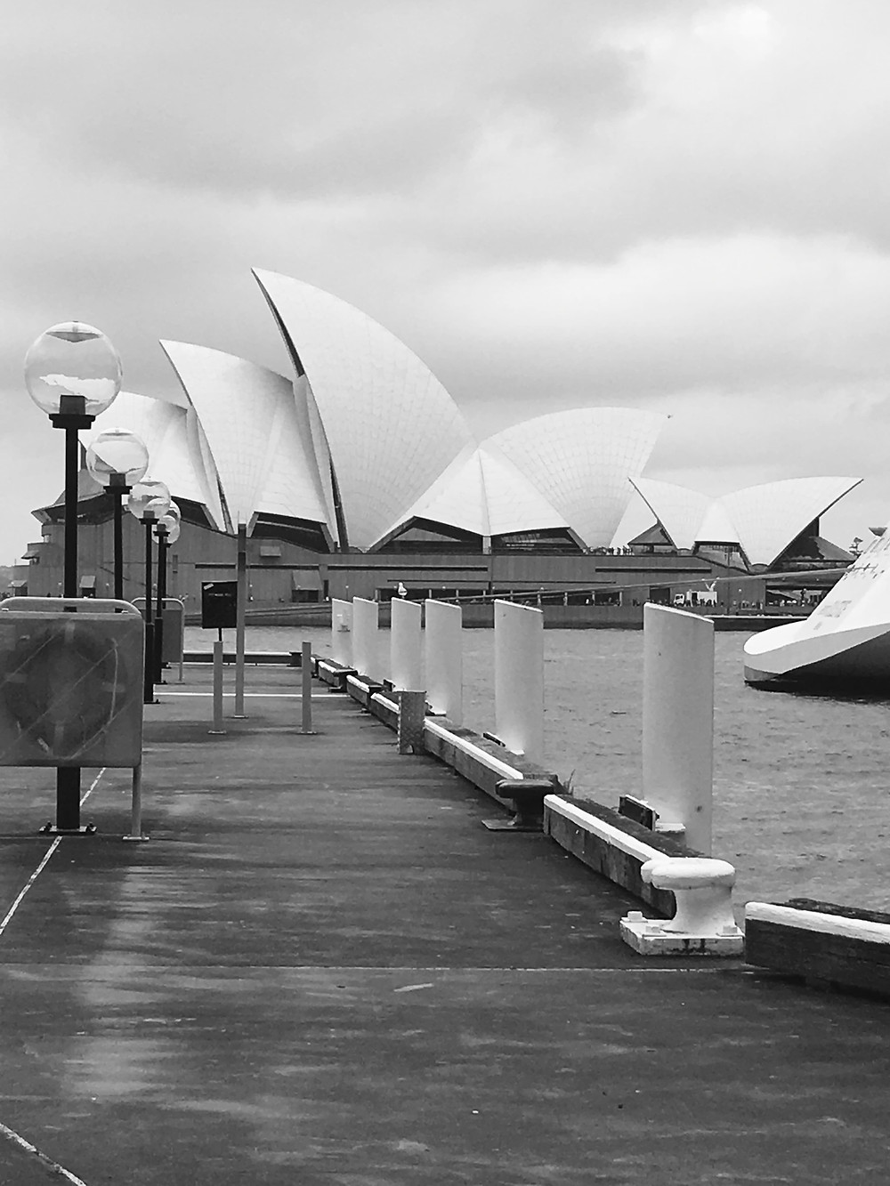 Black and white of the Sydney Opera House with a pier