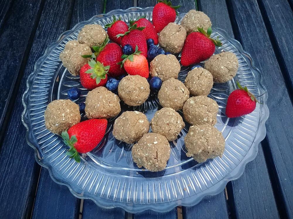 Vegan oatmeal raisin protein balls with fresh fruit on a platter