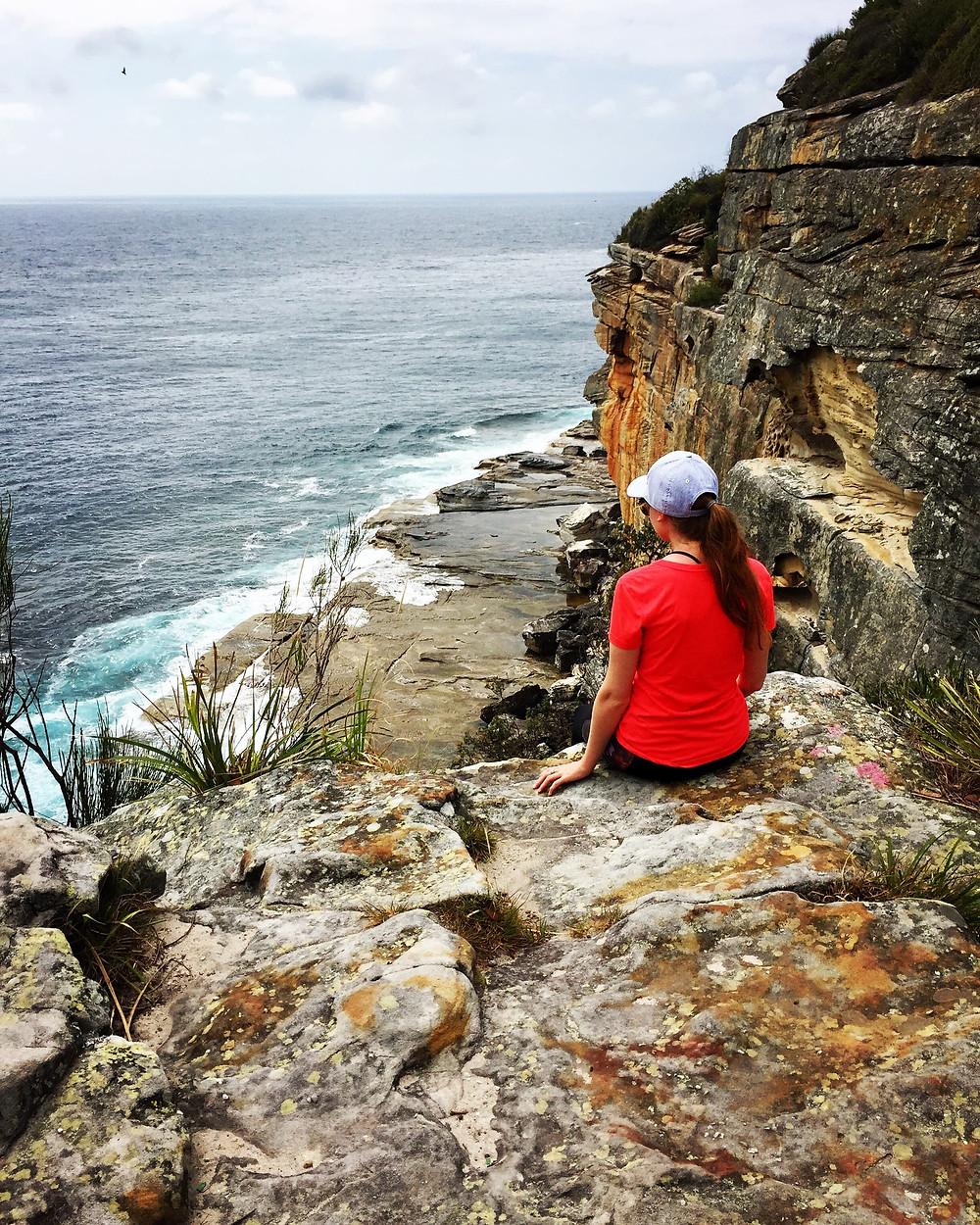 Girl sitting on cliff overlooking the ocean in Australia