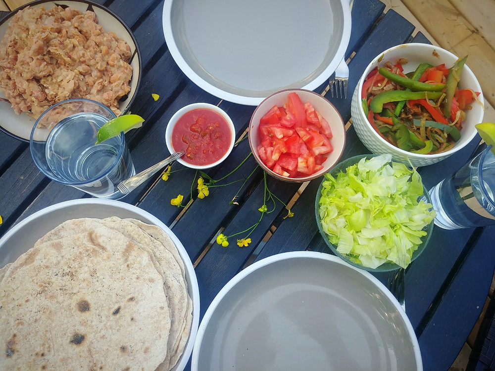 Preparing to eat burritos with homemade tortillas, refried beans, salsa and rice