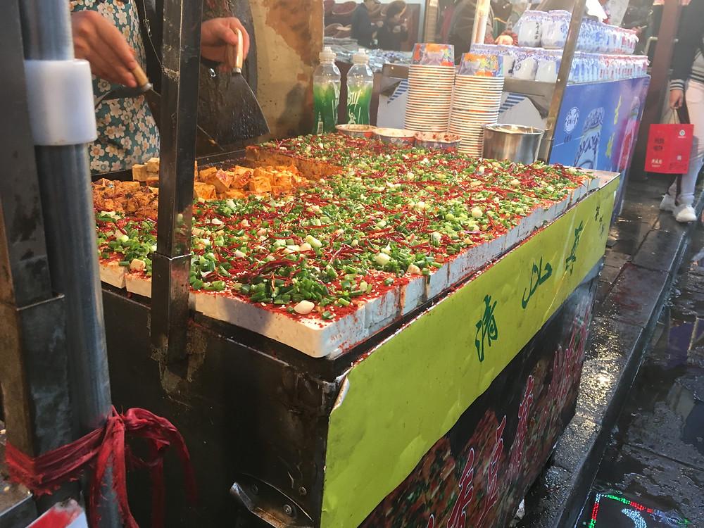 Xian street vendor serving chili seasoned tofu with green onions