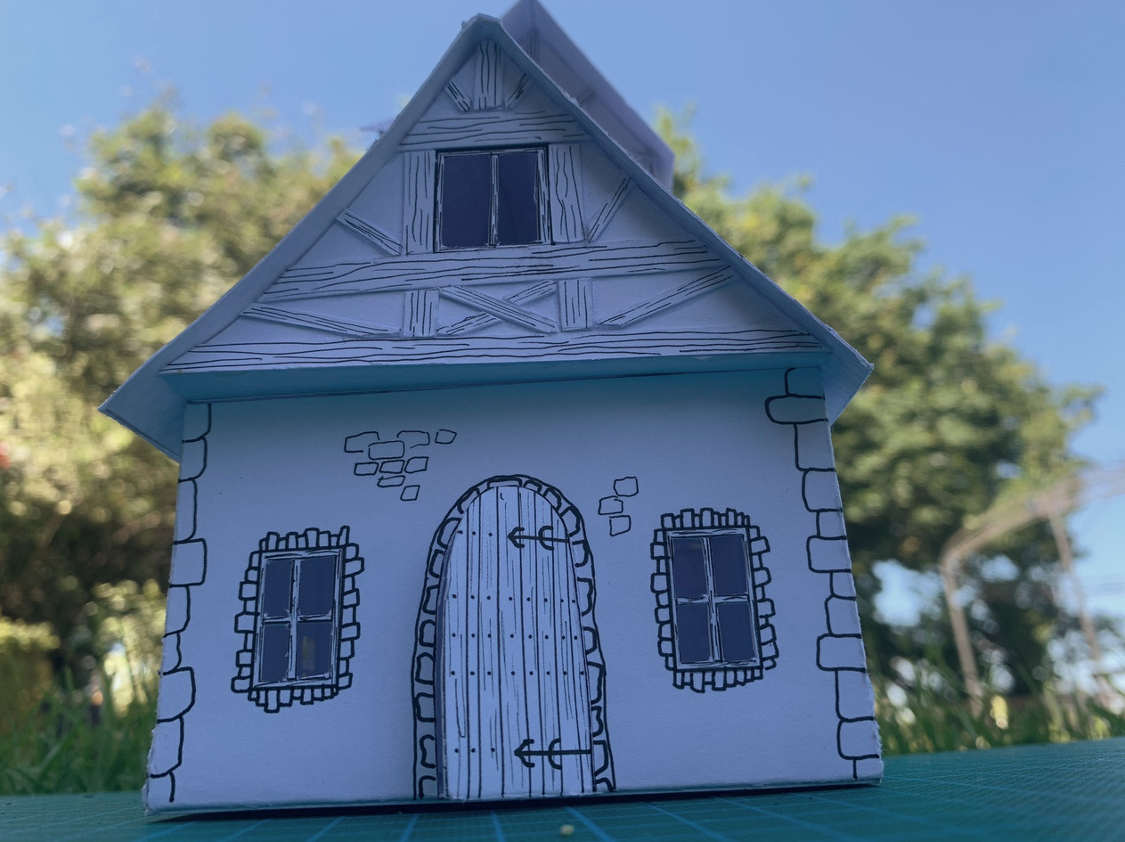 I made this white card model of a cottage for a fantasy film. The character that lives there is initially presented as good, but throughout the film we see them become 'bad'. To reflect this we wanted to build a nice looking cottage, but there are no 90 degree angles used. Most of these measurements are only slightly off, with the top floor the only immediately noticeable 'wonky' feature. The aim here was to make the viewer feel slightly uneasy the more time was spent in/around the house with the character, but it wasn't immediately obvious why