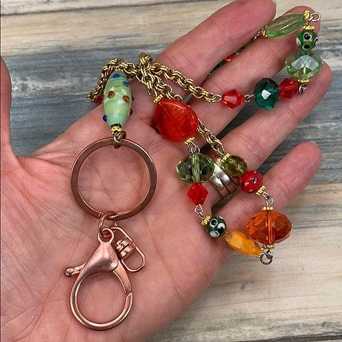 Glass bead assemblage orange green lanyard