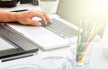 person sitting at computer with art supplies