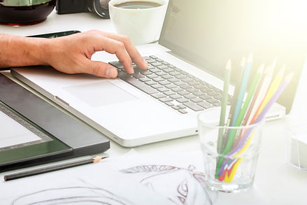 A male's left hand is positioned on a mac laptop computer keyboard, a full white coffee cup is in the background. In the foreground is a clear short glass filled with colorful pencils, sun shines brightly on the laptop screen. in front of the laptop is a black pad and a black pencil.